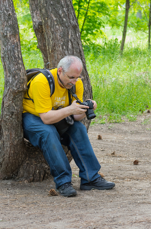 resent: Enthusiastic mature photographer scanning resent photos in the camera Stock Photo