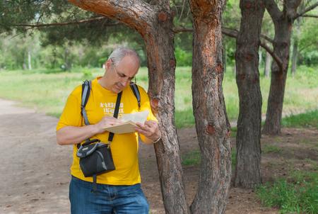 infatuation: Mature man reading outdoor under the tree shadow Stock Photo