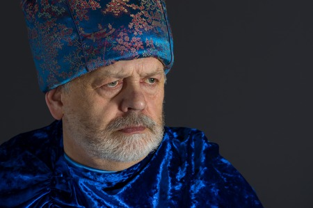 dictatorial: Nice portrait of senior man in blue oriental clothes against dark background