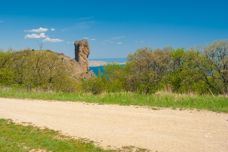 earth road: Spring landscape with earth road near Devil Finger crag in Karadag National park, Crimean peninsula Stock Photo