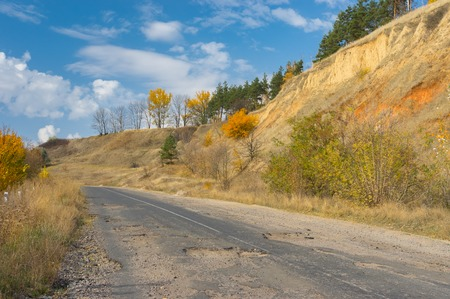 pit fall: Abandoned ruined rural road in central Ukraine at fall season Stock Photo