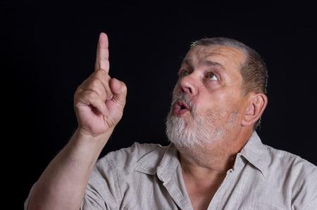 forefinger: Very emotional portrait of senior man pointing forefinger up