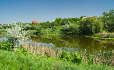 Ukrainian rural summer landscape with small river Sura in spring season.