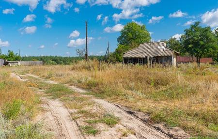 Landscape with sandy road and abandoned house in depopulating village Hetmanka, Poltavskaya oblast, Ukraine