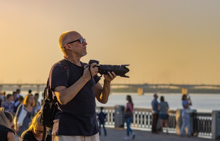 dnepr: DNEPR, UKRAINE - SEPTEMBER 10, 2016:Mature photographer looking out   people to shoot on Dnepr river embankment during City Day local activity
