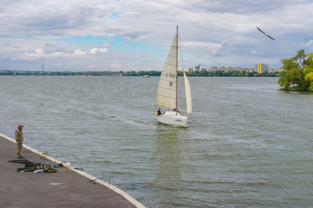 dnepr: DNEPR, UKRAINE - SEPTEMBER 24, 2016:Scenery with lonely fisherman, sailboat and flying gull on a Dnepr river embankment in center of Dnepr city at autumnal weekend