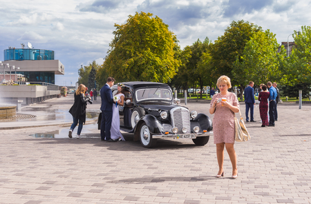 dnepr: DNEPR, UKRAINE - SEPTEMBER 24, 2016:Scenery with fiance, fiancee, vintage car, photographer and ordinary people on a Dnepr river embankment in center of Dnepr city at autumnal weekend