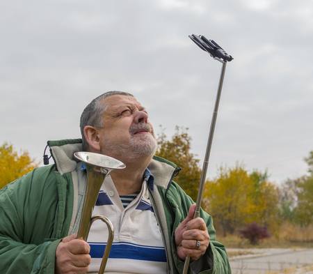 lunacy: Portrait of ridiculous senior man making faces while doing selfie outdoor