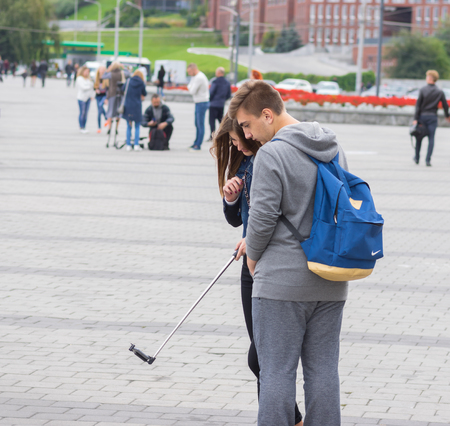 lunacy: DNEPR, UKRAINE - SEPTEMBER 24, 2016:Loving couple of teenagers making selfie on a Dnepr river embankment Editorial