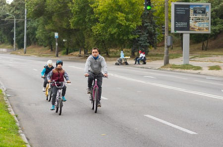 solicitous: DNEPR, UKRAINE - SEPTEMBER 25, 2016:Active young father with son and daughter having bicycle ride on a Dnepr river embankment at weekend