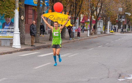 dnepr: DNEPR, UKRAINE - SEPTEMBER 25, 2016:Participant as a pacemaker with red balloon that shows desired time on a Dnepr Eco Marathon race on the city streets at September 25, 2016 in Dnepr, Ukraine