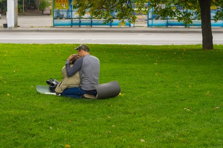 dnepr: DNEPR, UKRAINE - SEPTEMBER 25, 2016:Young loving couple sitting on a ground pad on green lawn on Dnepr river embankment in center of Dnepr city at autumnal weekend