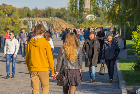 dnepr: DNEPR, UKRAINE - OCTOBER 02, 2016:Young loving couple walking together on a Dnepr river embankment in center of the Dnepr city at warm and sunny autumnal weekend Editorial