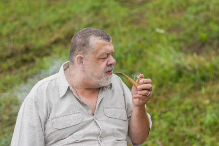concerned: Outdoor portrait of a senior man wearing light shirt smoking tobacco-pipe