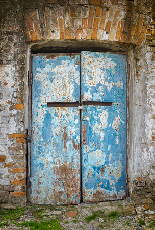 old doors: Old architectural details - door in an ancient building locked with small rusty padlock