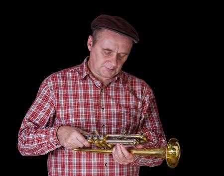 aerophone: Portrait of mature tuner examining the instrument - trumpet.