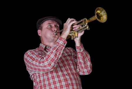 Portrait of mature trumpeter playing the instrument.