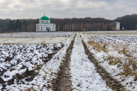 earth road: Fall landscape with an earth road leading to an ancient church of St. Nicholas (1797) in the urban settlement Dikanka, Ukraine