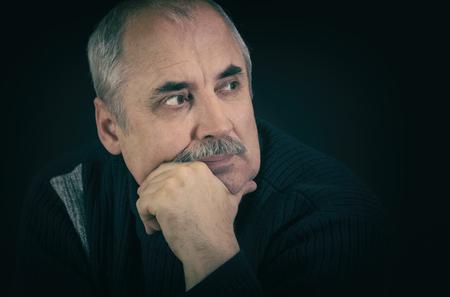 eloquent: Film toned portrait of mature Caucasian man thinking in darknes