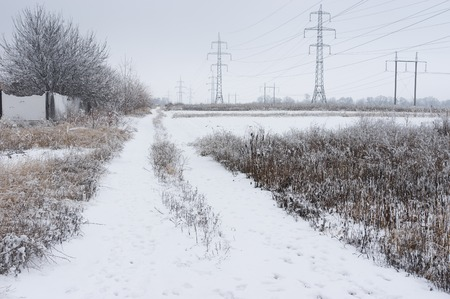 earth road: Country landscape with an earth road near high-voltage lines after hoar-frost attack