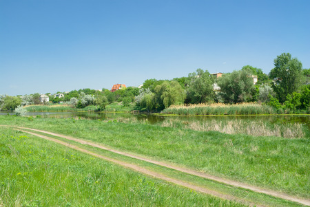 Ukrainian rural summer landscape with country road along small river Sura.