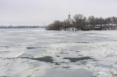 rushy: Winter landscape with frozen river Dnepr and Orthodox church on Monastyrsky island in Denpr city, Ukraine Stock Photo