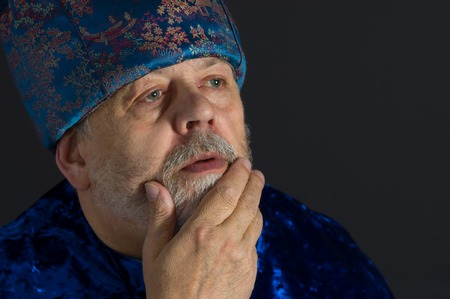 dictatorial: Portrait of meditating senior man in blue oriental clothes against dark background