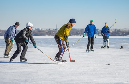Dnepr, Ukraine - January 22, 2017: People of different ages  playing hockey on a frozen river Dnepr in Ukraine