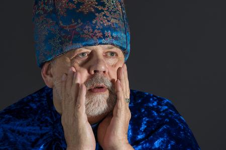 dictatorial: Portrait of anxious senior man in blue oriental clothes against dark background Stock Photo