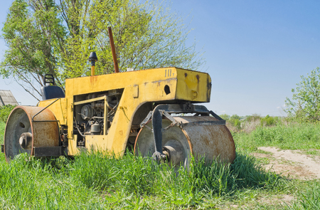 An old diesel road roller lost in grass.
