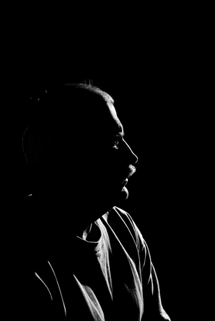 eloquent: Black and white portrait (low key, face outline) of a Caucasian man. Stock Photo