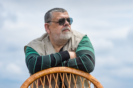 Outdoor portrait of senior man in black sunglasses leant on a wicker chair back and looking Stock Photo