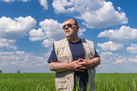 agronomist: Portrait of senior farmer standing inside unripe crops against blue, cloudy sky