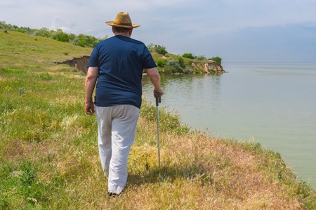 Lonely senior man in blue t-shirt and light pants walking on abrupt riverside of the Dnepr River, Ukraine