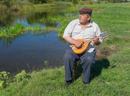 rushy: Senior man having rest on a riverside sitting on a wicker stool, singing and playing mandolin