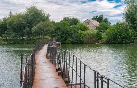 Old pedestrian pontoon-bridge over small river Schemylivka in outskirts of Dnipro city, Ukraine