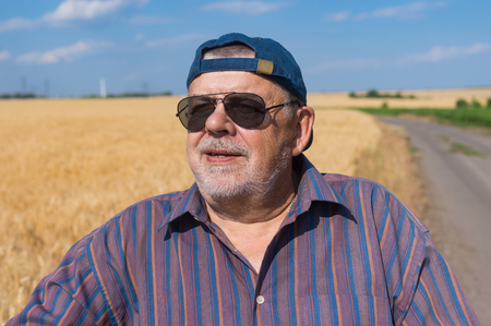agronomist: Outdoor portrait of smiling senior farmer standing at the wheat field edge and satisfied with future harvest