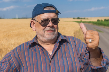 Outdoor portrait of a bearded senior man standing on a roadside beside agricultural field with ripe wheat Stock Photo