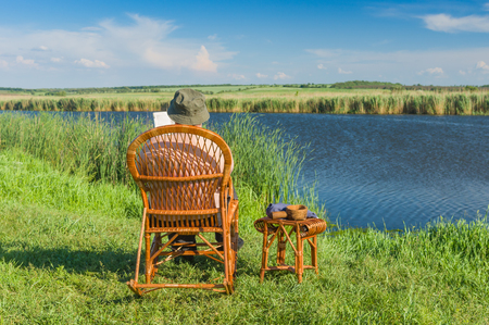Senior man reading book while sitting in the wicker rocking-chair on a riverside at summer season 免版税图像
