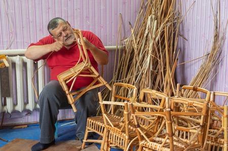 Senior master of wicker-work making kids chair