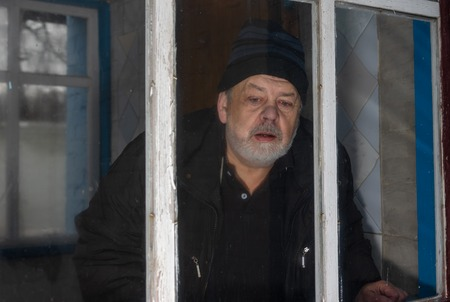 Senior man living alone in rural Ukrainian village peeping out through dirty window of his old house