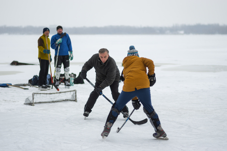 Dnipro, Ukraine - January 28, 2018: Teenager girl attacking small goal that mature man defending while playing hockey with mature men on a frozen river Dnipro in Ukraine