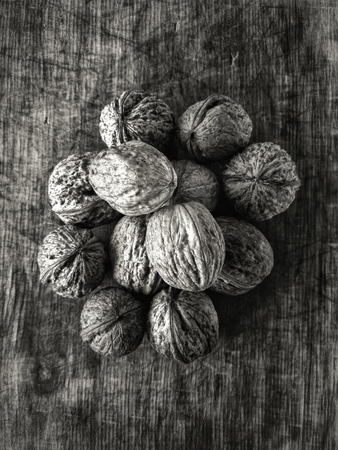 Top view on pile of walnuts lying on a scratched wooden surface. Black and white.