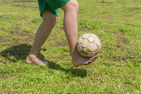 Barefoot amateur soccer player on old and bad field with shabby ball Stockfoto