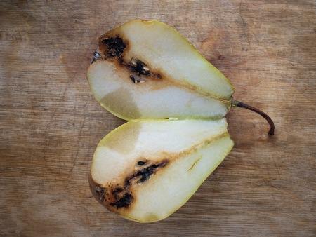 Top view on organic pear cut asunder lying on a wooden cut board