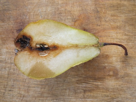 Top view on half of organic pear lying on a wooden cut board Banco de Imagens