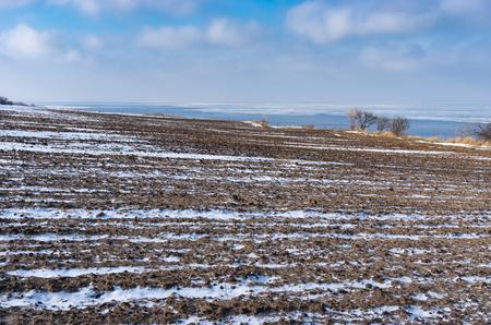 Winter landscape with ploughed fields near Kakhovka Reservoir on the Dnipro River, Skelki village, Ukraine 스톡 콘텐츠