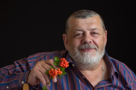 Nice low key portrait of a smiling senior man in striped shirt with small branch of Pyracantha shrub