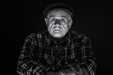 Nice black and white portrait of Caucasian senior man in cap - low key Reklamní fotografie