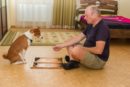 Young dog and mature man playing backgammon in bedroom